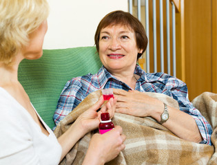 retirement home employee offering  mixture to aged patient