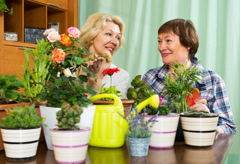 Two elderly women with flowerpots