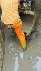 worker boots in brown mud during the flood 7