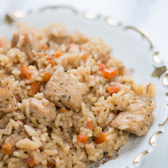 Close-up of pilaf with chicken in a glass plate, studio shot