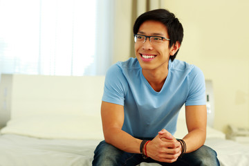 Happy asian man sitting on the bed at home