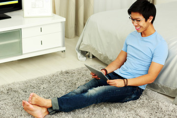 Smiling asian man sitting on the carpet with tablet computer