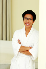 Happy asian man in bathrobe standing with arms folded at home