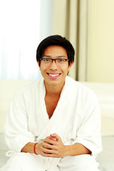 Smiling man in bathrobe sitting on the bed in bedroom