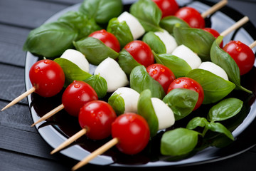 Kebabs with mozzarella, red tomatoes and green basil on a plate