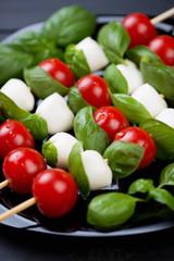 Kebabs with mozzarella balls, red tomatoes and basil, close-up