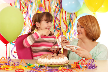 happy daughter and mother eat birthday cake