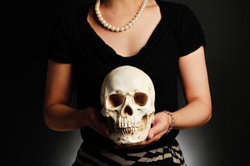 骸骨を手に持って真珠のネックレスをしている女性