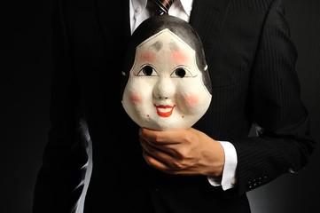 日本のお面を持ったスーツの男性
