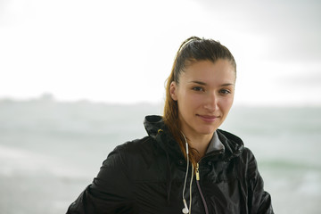 Portrait of young  woman, standing at beach in rainy day