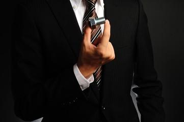 小さな部品を持っているスーツの男性
