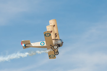 vintage British military WW1 triplane with a smoke trail