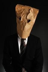 紙袋で顔を隠したスーツのビジネスマン