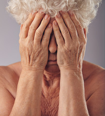Senior woman covering her face with hands