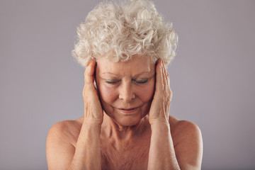 Old woman examining her skin condition