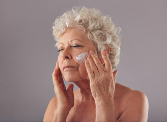 Senior woman applying anti-aging cream on her face