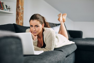 Pretty young female lying on sofa with a laptop