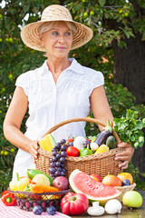 Woman with hat holding basket full of fruits and vegetables