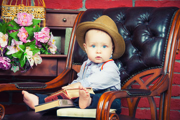 Baby gentleman sitting in a leather chair in the hat