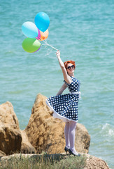 Happy redheaded girl with balloons looking at camera