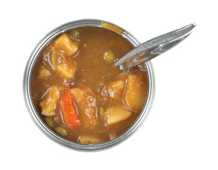 Tin can of vegetable stew with spoon inserted