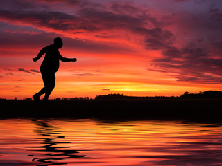 Silhouette of funny overweight man jogging by the lake