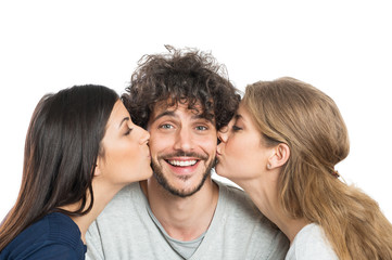 Women Kissing Man On Cheeks