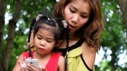 An asian girl and mother are playing funny game on smart phone