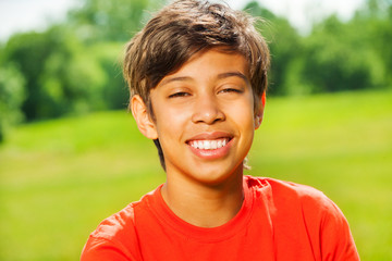 Brunet smiling boy in red T-shirt portrait