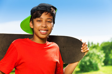 Cool boy in cap and with skateboard portrait