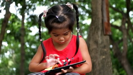 An asian girl playing funny game on tablet