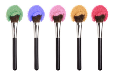 Cosmetics Makeup brushes with colorful powders.