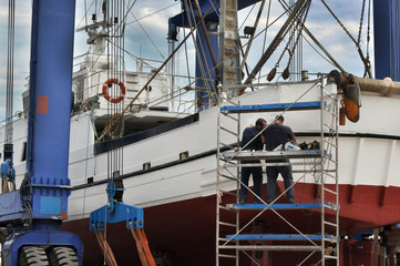 Operai riparano peschereccio in cantiere navale