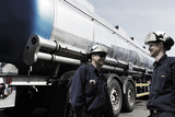oil workers and giant fuel-truck inside refinery - 68359838