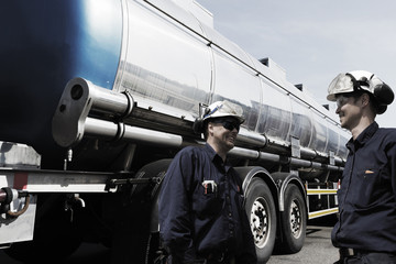 oil workers and giant fuel-truck inside refinery
