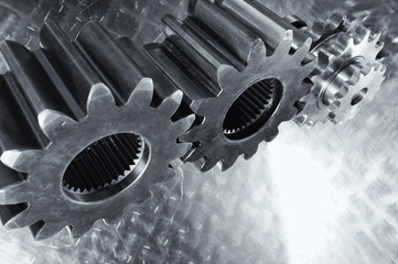titanium and steel gears and cogs against brushed aluminum