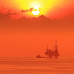 Silhouette Offshore Jack Up Drilling Rig and Boat At Sun Set Tim