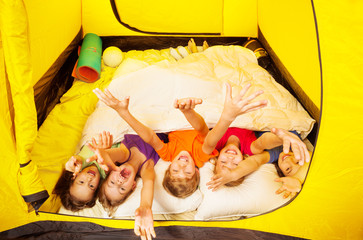 Five kids lay covered with blanket in a tent