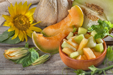 Fresh domestic cantaloupe melon on a wooden background