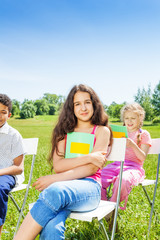 Three children hold notebooks and sit on chairs