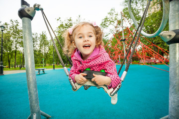 Laughing girl laying and swinging on swing set