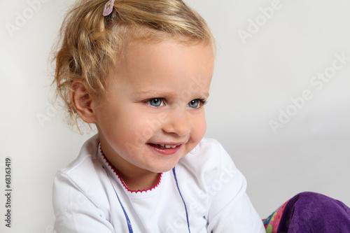 canvas print picture lachendes kleines Mädchen mit lila Hose