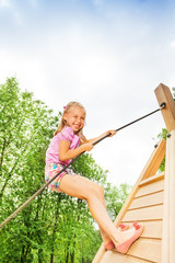 Smiling girl climbs on wooden construction