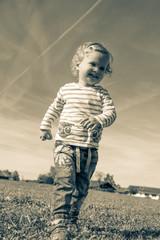 kleines Mädchen rennt über die Wiese