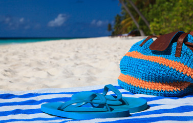 Straw bag, towel and flip flops on a tropical beach