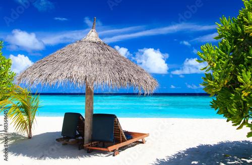 Beach chairs on tropical beach - 68364645