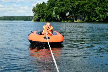 kleiner Junge fährt mit einem Schlauchboot