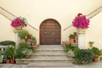 elegant doorsteps to italian villa decorated with many flowers