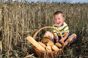 kleiner Junge im Kornfeld mit einem Brotkorb