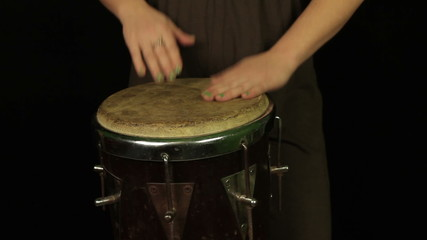 Female hands playing on the drum